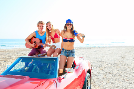 convertible car: young group having fun on the beach playing guitar and dancing in a convertible car Stock Photo
