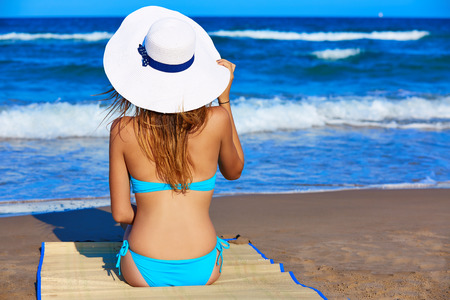 Girl young sitting looking at the sea with beach hat rear back view