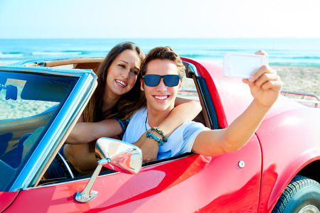 convertible car: young couple selfie happy in a red convertible car at the beach Stock Photo