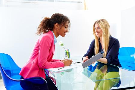entrevista de trabajo: empresarias entrevistan a satisfacer múltiples africand étnica y rubia sentada en la oficina