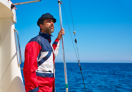 Beard sailor man sailing sea ocean in a boat with captain cap