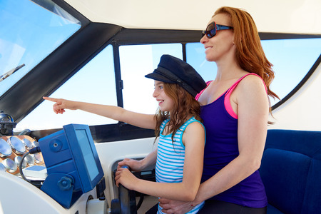 mother to be: Kid girl pretending be a captain sailor cap with her mother in boat indoor