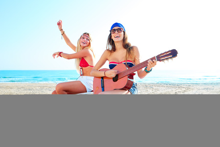 convertible car: girls having fun playing guitar on th beach with a convertible car Stock Photo