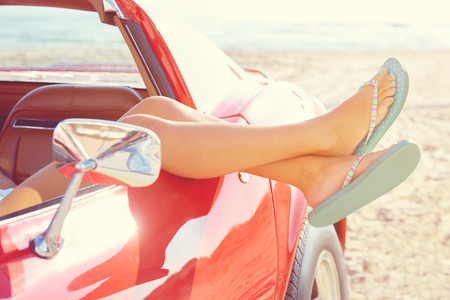 Relaxed woman legs and flip flops in a car window on the beach Archivio Fotografico