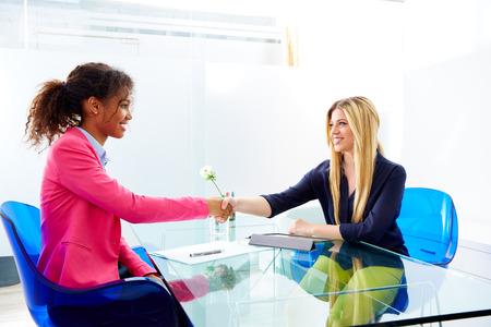 entrevista: apretón de manos entrevista empresarias múltiples africand étnica y rubia sentada en la oficina
