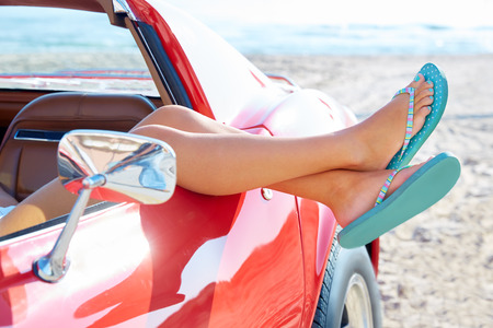 Relaxed woman legs and flip flops in a car window on the beach Stockfoto