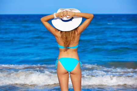 Girl young standing looking at the sea with beach hat rear back view