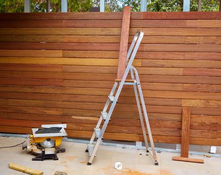Ipe installatie houten omheining met timmerman tafel cirkelzaag en zaagsel Stockfoto