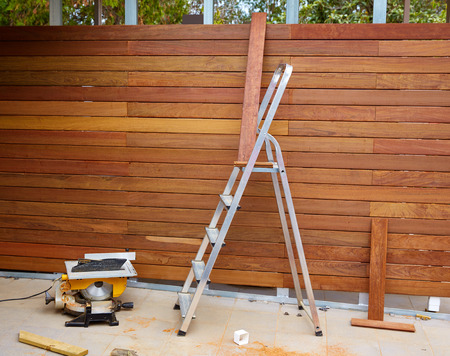 installations: Ipe wood fence installation with carpenter table circular saw and sawdust