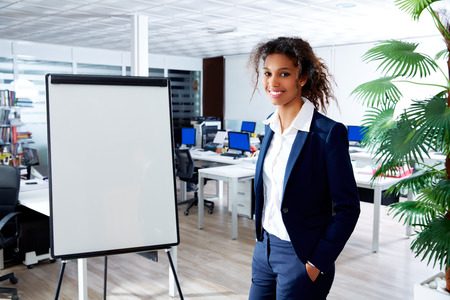 african ethnic executive woman with presentation board in office standing happy Фото со стока