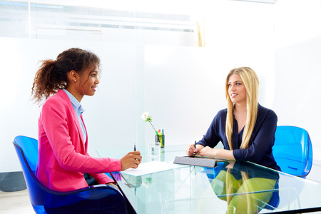 multi ethnic: businesswomen interview meeting multi ethnic africand and blond sitting at office
