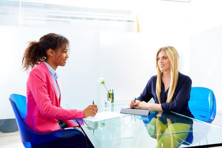 entrevista de trabajo: empresarias entrevistan a satisfacer m�ltiples africand �tnica y rubia sentada en la oficina