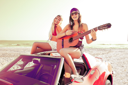young  brunette: girls having fun playing guitar on th beach with a convertible car Stock Photo