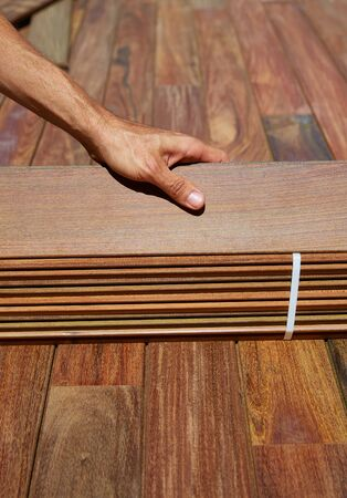 decking: Ipe decking installation with carpenter hands holding tropical wood slats