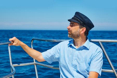 freshwater sailor: Beard sailor man sailing sea ocean in a boat with captain cap looking horizon