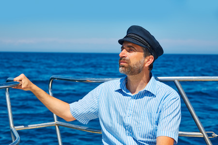 Beard sailor man sailing sea ocean in a boat with captain cap looking horizon