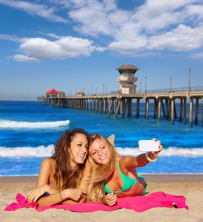girls in bikini: happy girl friends selfie portrait beach sand in California photo mount