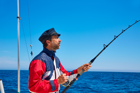 freshwater sailor: Beard sailor man fishing rod trolling in saltwater in a boat trolling with captain cap Stock Photo