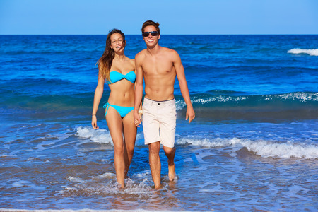 teen bikini: Beautiful young couple walking in the beach shore on summer vacation