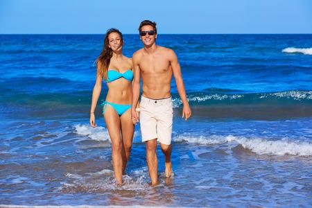 pareja adolescente: Hermosa joven pareja caminando en la orilla de la playa en las vacaciones de verano