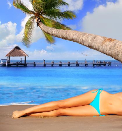 chica sexy: bikini piernas de la muchacha que mienten en arena de la playa en verano palmera foto montaje Foto de archivo
