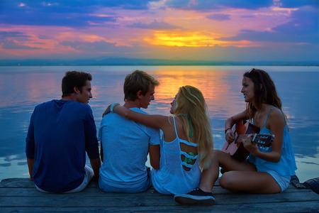 mujer bonita: Grupo de amigos tocando la guitarra en el muelle puesta de sol al atardecer playa feliz