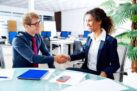mujer trabajadora: Executive handshake blond businessman and african businesswoman in office meeting