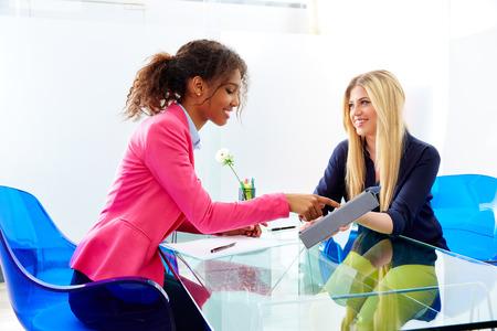 liderazgo empresarial: empresarias entrevistan a satisfacer múltiples africand étnica y rubia sentada en la oficina