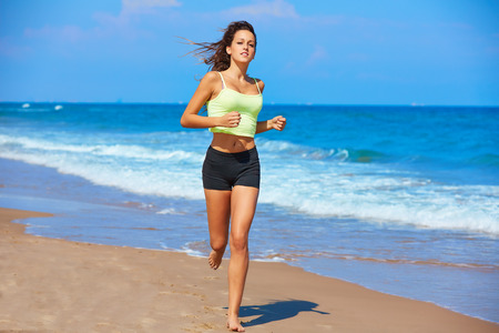 running water: Beautiful brunette girl running in the beach at summer vacations