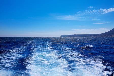 Denia San Antonio Cape in Alicante sailing with boat wake at Spain photo