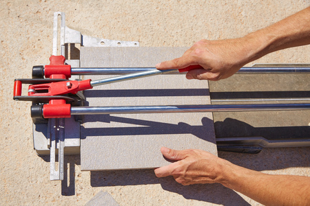 tile cutter: tile cutter machine with mason hands cutting tiles