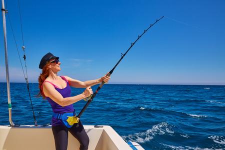 trolling: Mujer hermosa chica barra de pesca de arrastre en el agua salada en un barco de pesca de arrastre