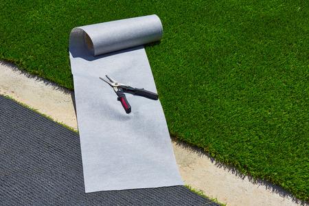 pasto sintetico: Instalación de césped artificial en el jardín de césped con las herramientas y rollo conjunta