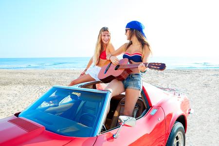 convertible car: girls having fun playing guitar on th beach with a convertible car Stock Photo