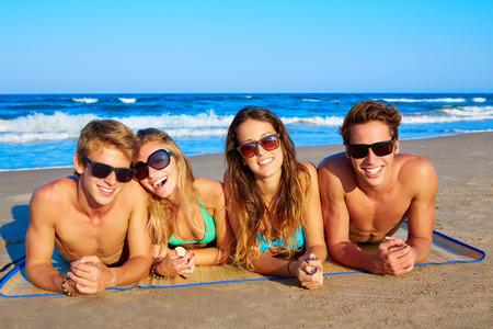 Group of young friends couples portrait in beach lying on sand at summer vacation photo