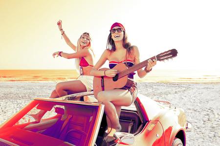 niñas jugando: muchachas que se divierten tocando la guitarra en el th playa con un coche descapotable