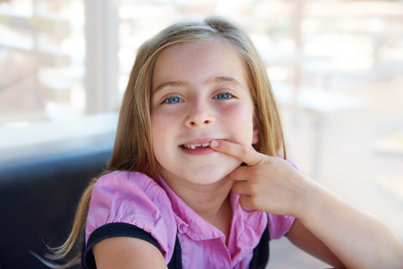 sweet tooth: Blond happy kid girl showing her indented teeth portrait