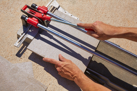 cutting machine is: tile cutter machine with mason hands cutting tiles