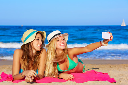 deitado: feliz menina amigos selfie retrato que encontra-se na praia da areia em férias de verão