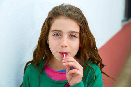 suck: Beautiful blue eyes kid gils eating a lollipop sweet portrait Stock Photo