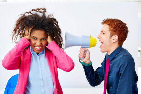bad leadership: businessman talking in megaphone to african executive with scared expression