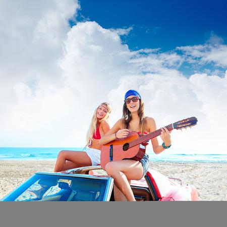 女の子楽しんでコンバーチブル回ビーチでギターを弾く