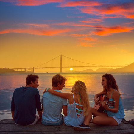 teen bikini: Friends group playing guitar in sunset pier at dusk in San francisco photo mount