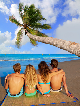 friends group couples sitting in beach sand rear view back palm tree photo mount photo