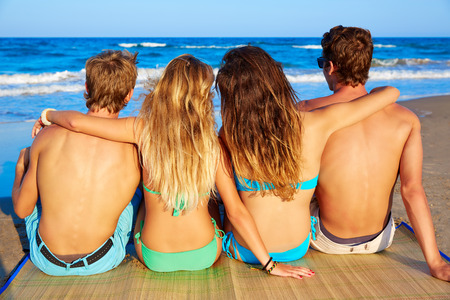 friends group couples sitting in beach sand rear view back looking to the sea photo