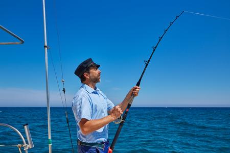 trolling: Barba marinero curric�n ca�a de pescar en agua salada en un barco de arrastre con el casquillo del capit�n Foto de archivo