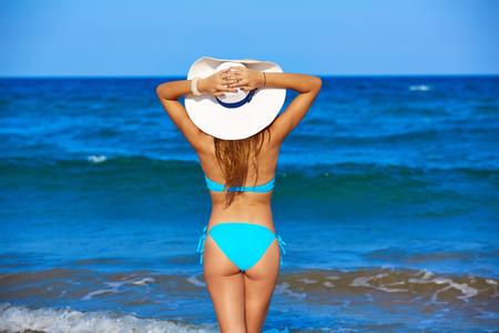 Jeune fille debout regardant la mer avec chapeau de plage arrière vue arrière