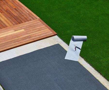 pasto sintetico: Instalación de césped de hierba artificial en la cubierta jardín con herramientas y rollo conjunta Foto de archivo