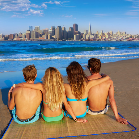 rear view girl: friends group couples sitting in beach sand rear view San Francisco skyline photo mount