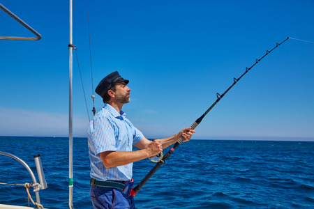 Beard sailor man fishing rod trolling in saltwater in a boat trolling with captain cap Stock Photo
